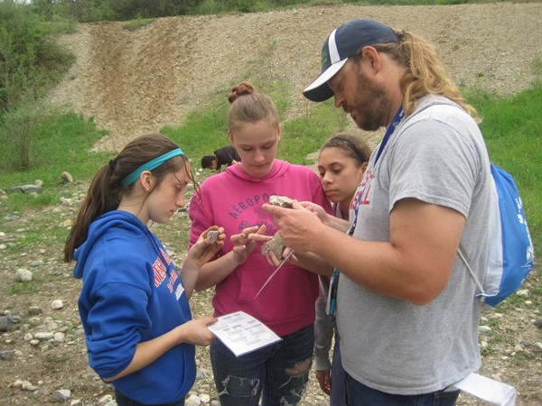 Science teacher Mr. Swank on a Rock Cycle scavenger hunt at Merry Lea with some 7th graders.