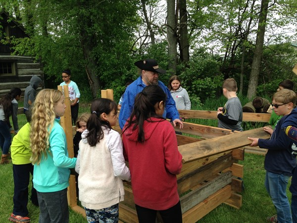 Students from Mrs. Lemler's class build a log cabin at Pioneer Day.