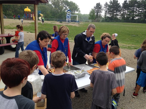 Staff at WNE serve students a tasty lunch at our annual school picnic.