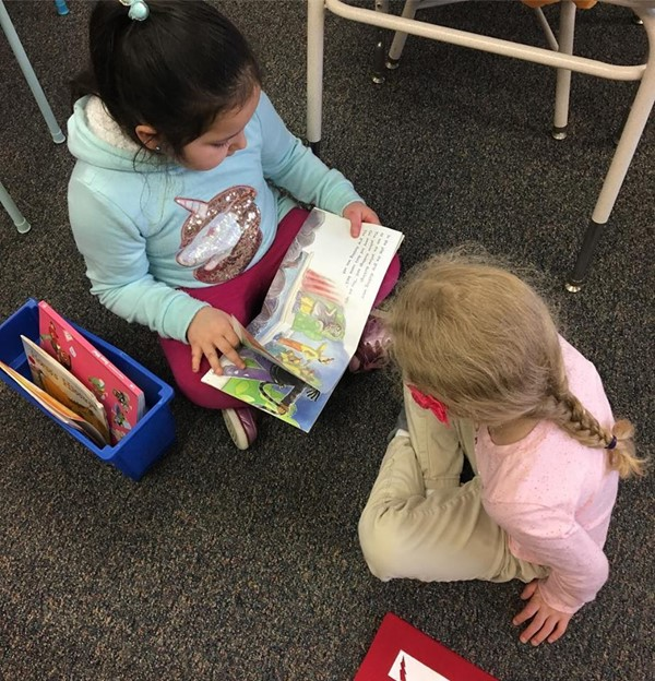 First graders reading to kindergartners.
