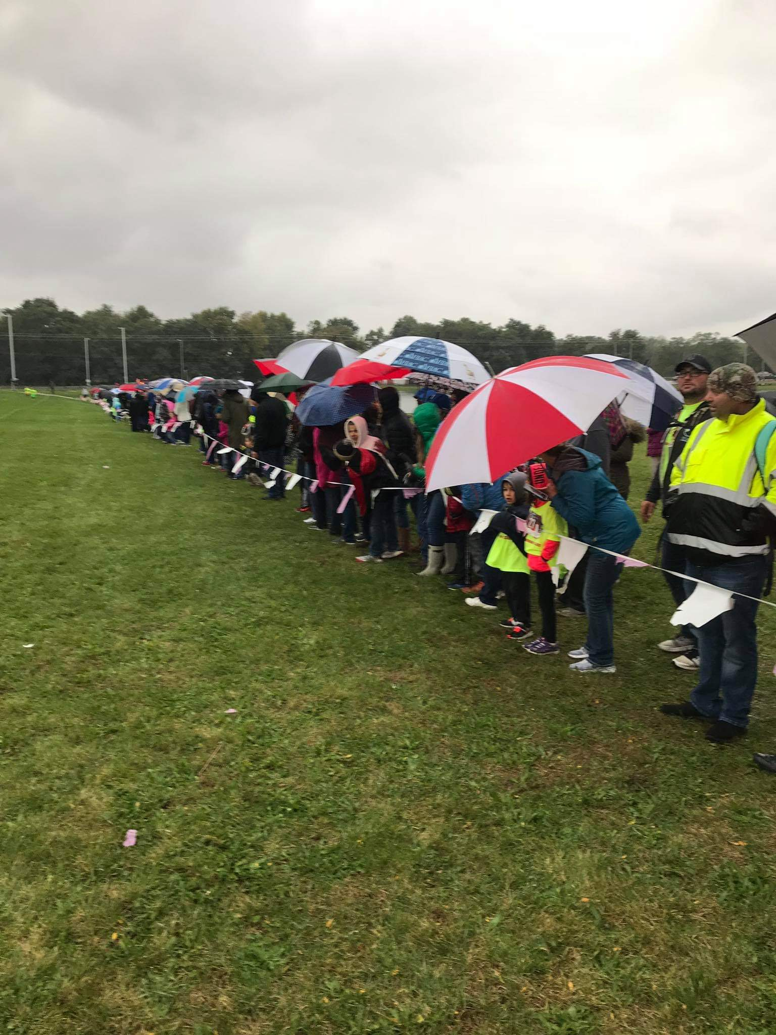 Parents with blankets and umbrellas cheer on the runners.
